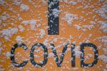 Заснеженный знак с надписью Covid указывает путь к тесту мазка для персонала в городской больнице Дрездена