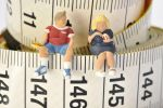Overweight figures sitting on a tape measure