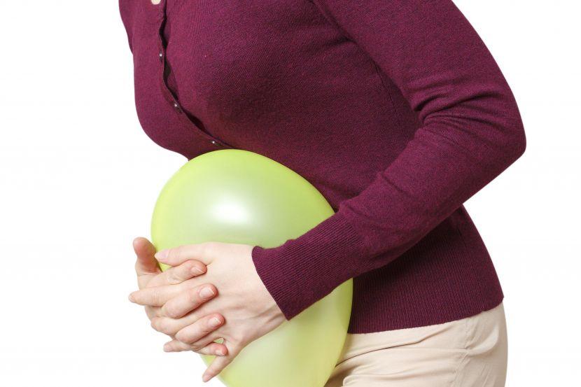 Женщина, прижимающая воздушный шар к животу, символическое изображение спазмов в животе, боли в животе, несварения желудка, раздраженного кишечника, ПМС, пищевой непереносимости, вздутия живота.
