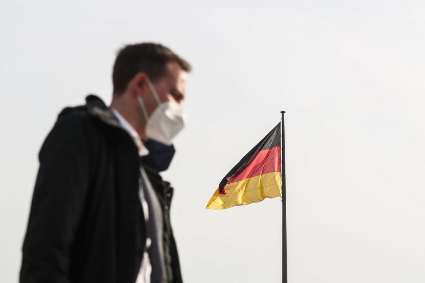 A pedestrian wearing face mask walks past a German national flag.