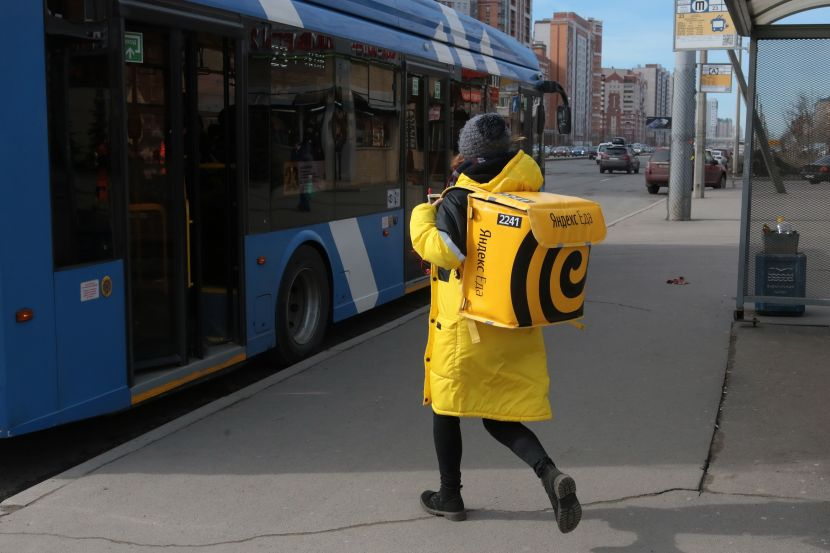 The girl with a big backpack of yellow color with Yandex emblem food rasnosit food for clients